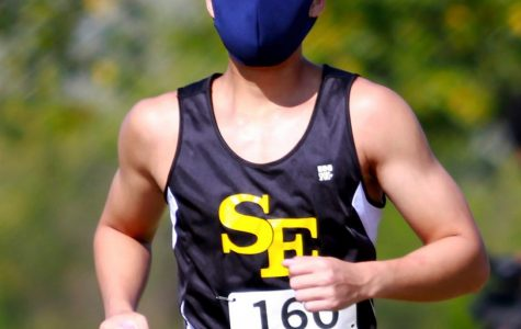Sr. Minh-Tri Bui wears a mask as he runs in a cross country meet at Cessna Activity Center.